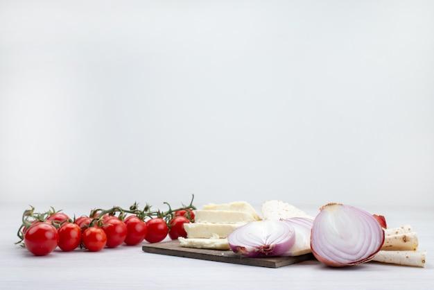 Vista frontal de tomates vermelhos frescos junto com queijo branco e cebola no branco