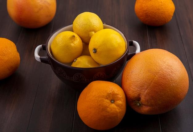 Vista frontal de toranja com laranjas e limões em uma panela com fundo de madeira