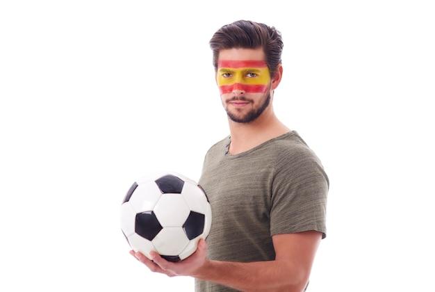 Vista frontal de torcedores dedicados da espanha com bola de futebol