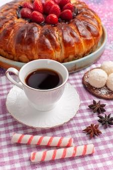 Vista frontal de torta de morango deliciosa com xícara de chá rosa