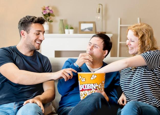 Vista frontal de três amigos comendo pipoca no sofá