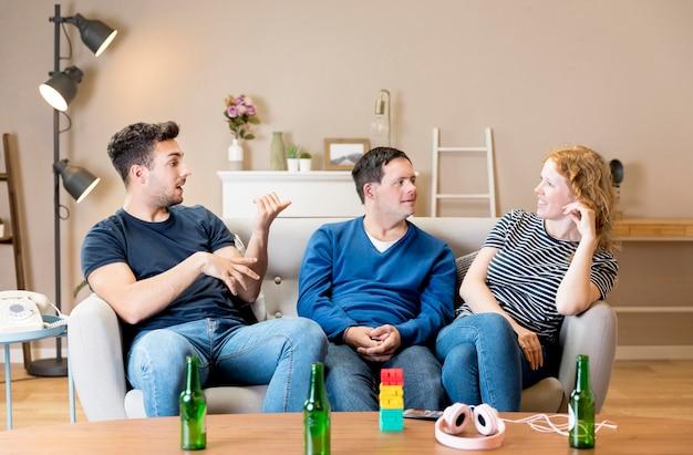 Vista frontal de três amigos em casa tomando uma cerveja