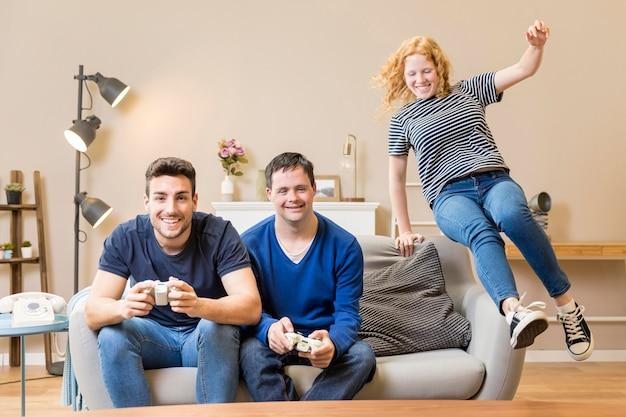 Vista frontal de três amigos jogando videogame