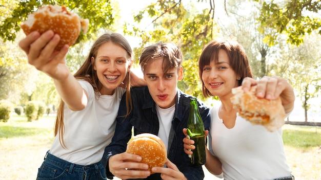 Vista frontal de três amigos no parque com hambúrgueres e cerveja