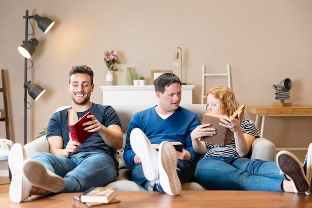 Vista frontal de três amigos segurando livros