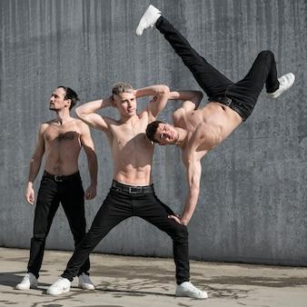 Vista frontal de três artistas de hip-hop sem camisa posando