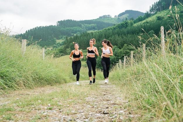 Vista frontal de três belas mulheres correndo em um caminho através de uma floresta