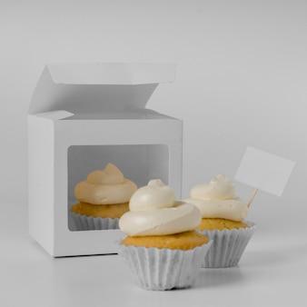 Vista frontal de três cupcakes com caixa de embalagem