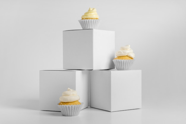 Vista frontal de três cupcakes com embalagem com caixas