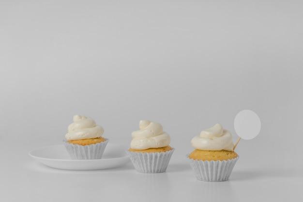 Vista frontal de três cupcakes com embalagem e espaço de cópia