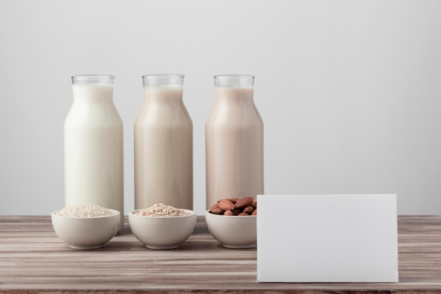 Vista frontal de três garrafas com leite diferente