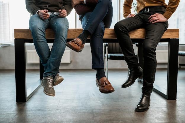 Vista frontal de três homens conversando no escritório durante uma reunião