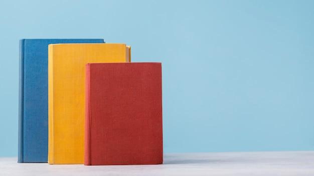 Vista frontal de três livros coloridos com espaço de cópia