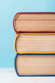 Vista frontal de três livros empilhados coloridos