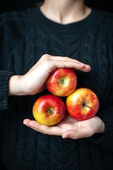 Vista frontal de três maçãs vermelhas maduras em mãos femininas