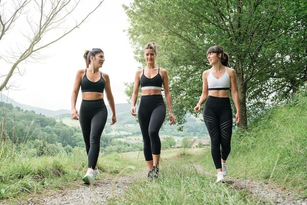 Vista frontal de três mulheres conversando e caminhando por um caminho através de uma floresta antes de sair para uma corrida