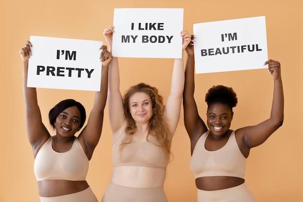 Vista frontal de três mulheres segurando cartazes com declarações de positividade corporal