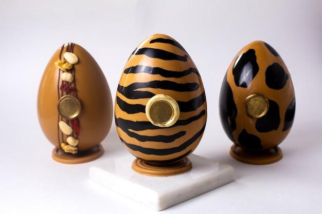 Vista frontal de três ovos de chocolate em ouro e preto nas cores tigre e leopardo de ouro em stand