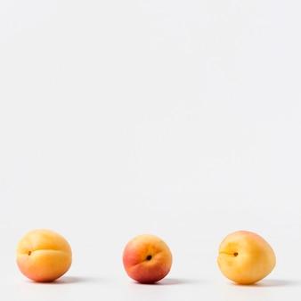 Vista frontal de três pêssegos com espaço de cópia