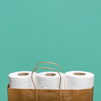 Vista frontal de três rolos de papel higiênico em saco de papel com espaço de cópia