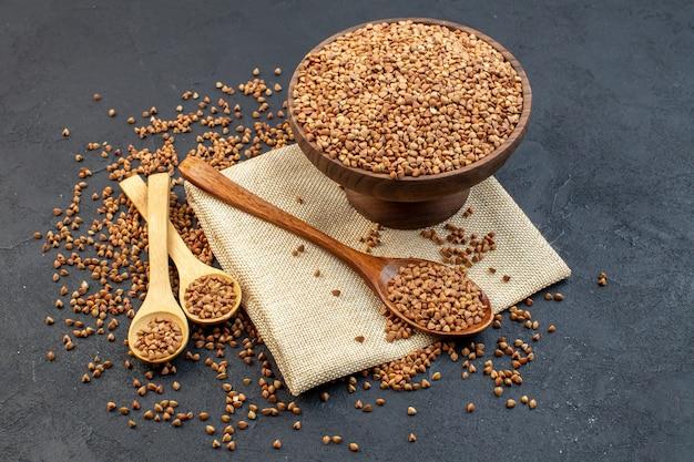 Vista frontal de trigo sarraceno marrom dentro do prato com um par de colheres em fundo escuro