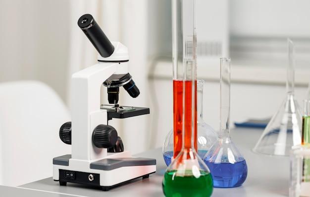 Vista frontal de tubos de ensaio e microscópio no laboratório