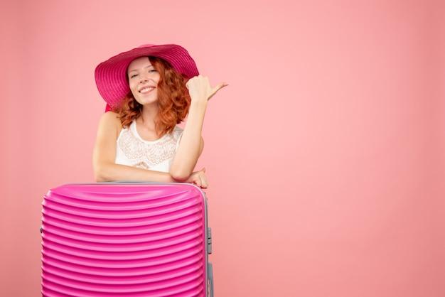 Vista frontal de turista com bolsa rosa na parede rosa