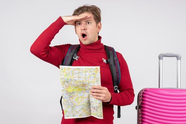 Vista frontal de turista masculino com mochila e mapa na parede branca
