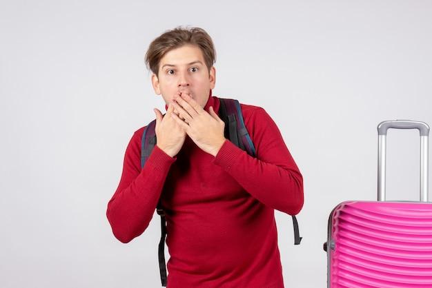 Vista frontal de turista masculino com mochila na parede branca