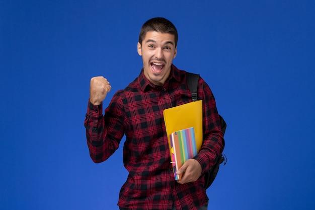 Vista frontal de um aluno do sexo masculino com camisa quadriculada vermelha com mochila segurando arquivos e cadernos regozijando-se na parede azul