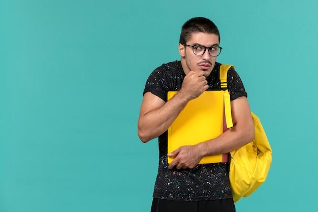 Vista frontal de um aluno do sexo masculino em uma mochila de camiseta amarela escura segurando diferentes arquivos na parede azul clara