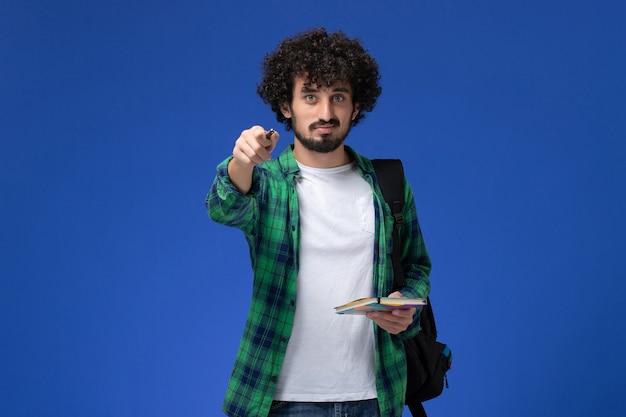 Vista frontal de um aluno do sexo masculino usando uma mochila preta segurando um caderno e uma caneta