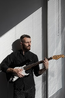 Vista frontal de um artista masculino posando ao lado da janela enquanto toca guitarra elétrica