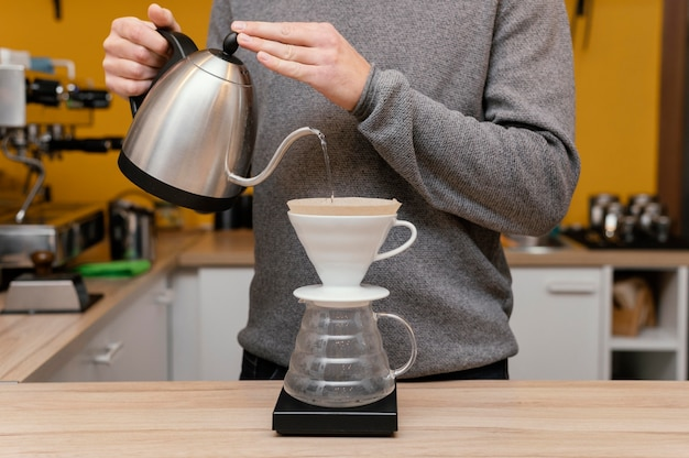 Vista frontal de um barista derramando água quente no filtro de café