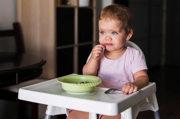 Vista frontal de um bebê triste comendo