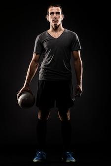 Vista frontal de um belo jogador de rugby segurando uma bola