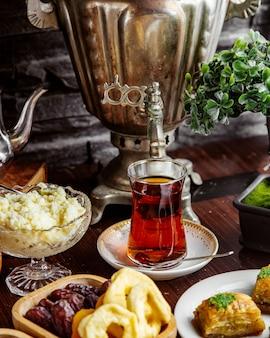 Vista frontal de um bule de samovar com uma xícara de chá com frutas secas