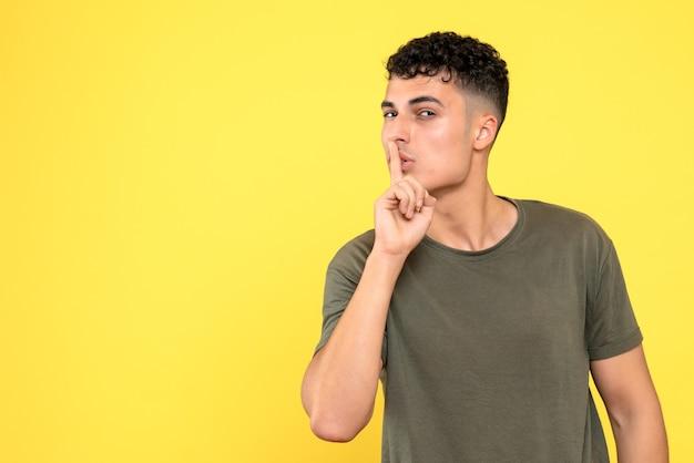 Vista frontal de um cara que o cara segura um dedo perto dos lábios e parece astuto