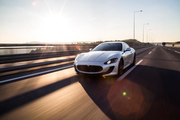 Vista frontal de um carro esporte prateado de alta velocidade, dirigindo na estrada.