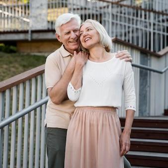 Vista frontal de um casal apaixonado de idosos posando ao ar livre