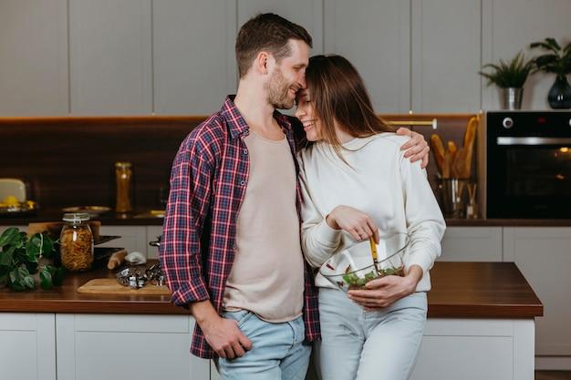 Vista frontal de um casal apaixonado preparando comida em casa