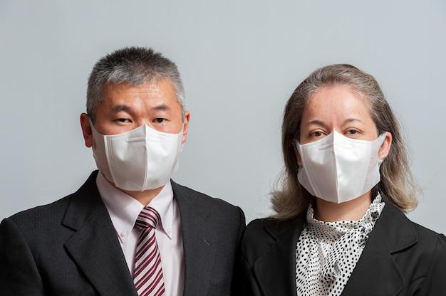 Vista frontal de um casal asiático de meia-idade com roupa formal e máscara cirúrgica branca