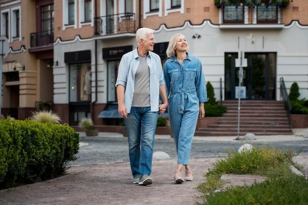 Vista frontal de um casal de idosos abraçado, aproveitando seu tempo na cidade