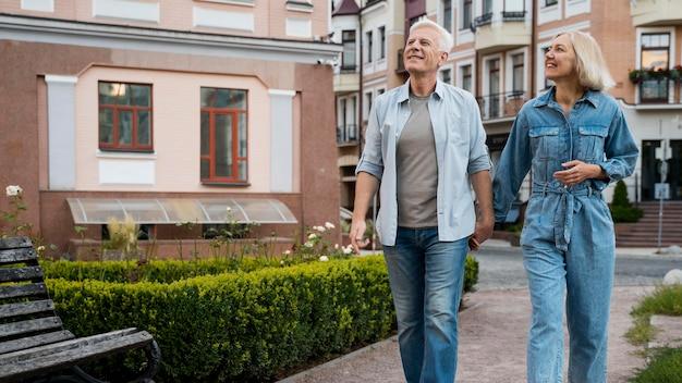 Vista frontal de um casal de idosos de mãos dadas na cidade