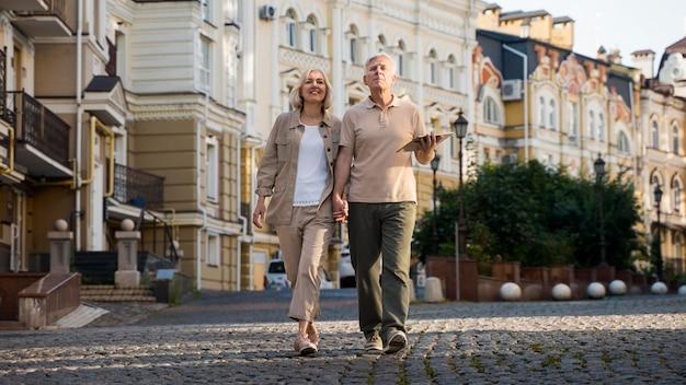 Vista frontal de um casal de idosos em um passeio pela cidade com um tablet