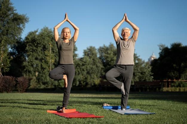 Vista frontal de um casal de idosos fazendo ioga ao ar livre