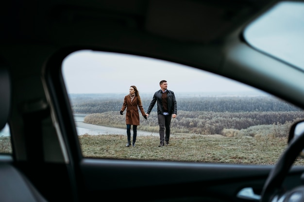 Vista frontal de um casal de mãos dadas do lado de dentro do carro