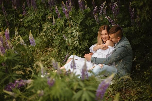 Vista frontal de um casal grávido sentado na grama em um campo de tremoço