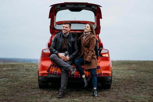 Vista frontal de um casal sentado no porta-malas do carro
