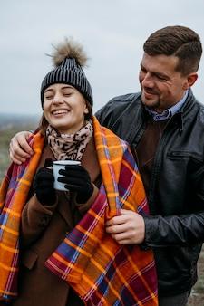 Vista frontal de um casal sorridente ao ar livre com um cobertor e uma bebida quente